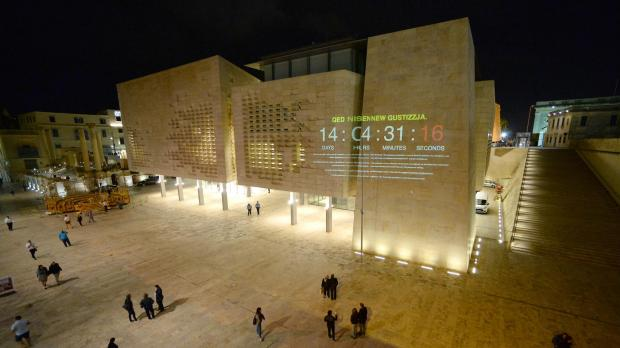 People read a message projected on the Parliament walls in Valletta by the Civil Society Network activists on October 30 demanding justice following the murder of Daphne Caruana Galizia. Photo: Matthew Mirabelli