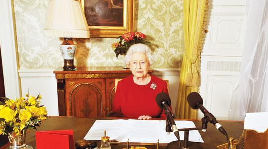 Queen Elizabeth II sitting at a desk in Buckingham Palace, central London, after recording her Commonwealth Day address that is broadcast across the world. Photo: John Stillwell/PA Wire