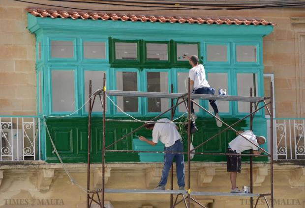 Three men at work, restoring and painting a traditional wooden balcony in Sliema on October 8. Photo: Matthew Mirabelli