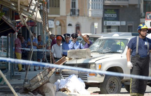 Residents watch as police officers secure the area after the construction site fatality in Gżira on August 7. Photo: Matthew Mirabelli