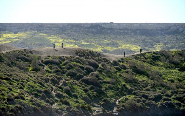 People make their way along the clay slopes at the top of Ghajn Tuffieha Bay on February 7. Photo: Matthew Mirabelli
