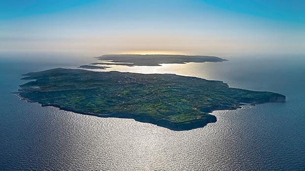 Gozo from the air, silhouetted.
