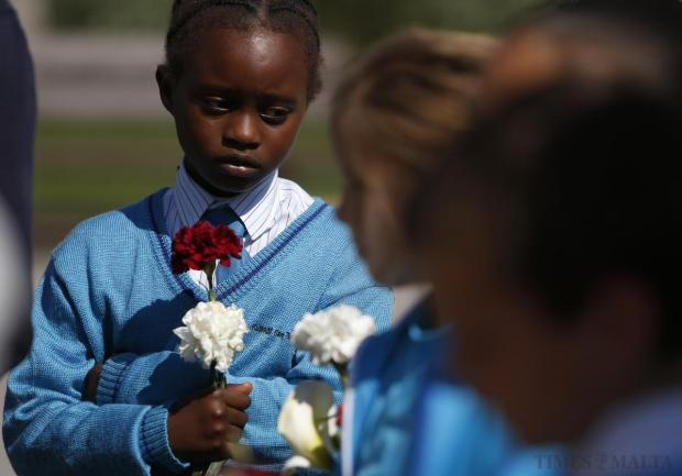 Schoolgirls from St Theresa College Primary School hold flowers during a memorial service for migrant victims in Msida on April 22. Photo: Darrin Zammit Lupi