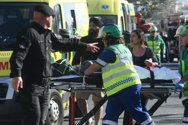 Emergency crews rush an injured passenger into an ambulance. Photo: Jonathan Borg
