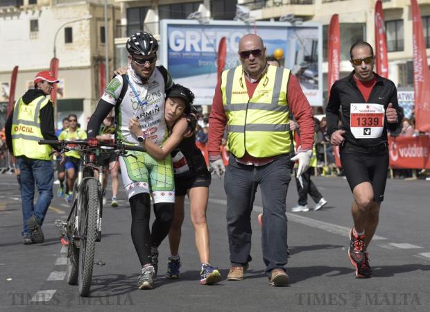 An exhausted Malta Marathon runner is helped towards the finsihing line by a cyclist and a race steward in Sliema on 28 February. Photo: Mark Zammit Cordina