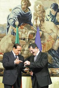 Italy`s new Prime Minister Romano Prodi rings a silver bell, to signify the start of his first Cabinet meeting, after taking office from former Prime Minister Silvio Berlusconi at Chigi palace in Rome, yesterday.