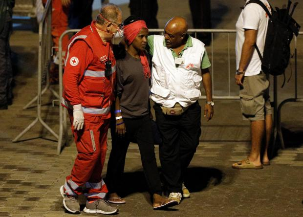 An unaccompanied minor migrant is helped after disembarking from the Italian coast guard vessel Diciotti.