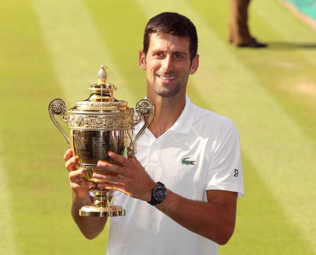 Novak Djokovic holds the Wimbledon trophy, on Sunday.