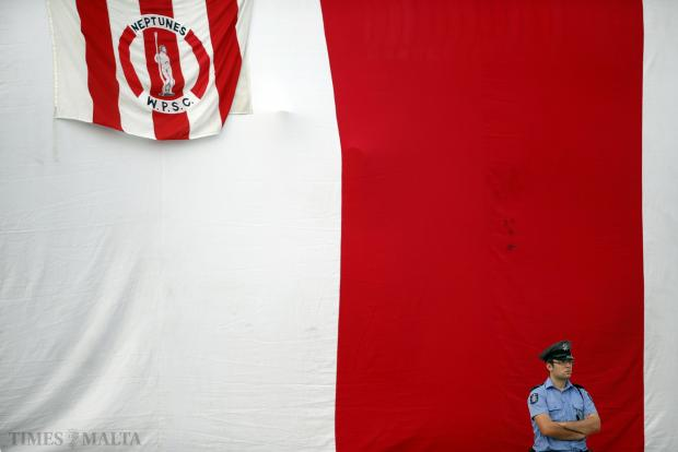 A police officer stands beneath a large Neptunes flag before the start of the waterpolo league decider between Neptunes and San Giljan at the National Pool on September 3. Photo: Darrin Zammit Lupi