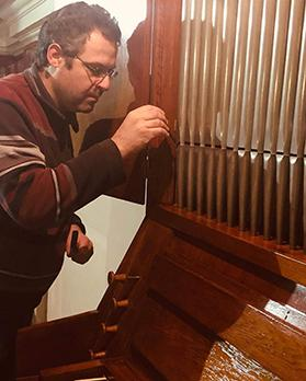 Robert Buhagiar at work voicing a facade pipe at Senglea Oratory. Above: The Frobenius pipe organ during and after its installation at Sliema.