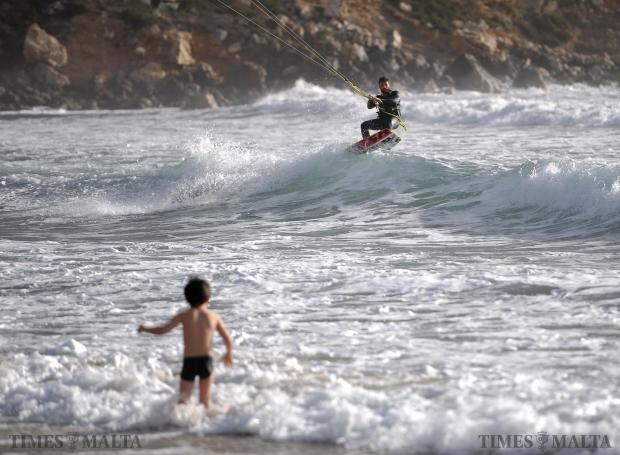 A child and a kite surfer brave the winter sea at Golden Bay on February 10. Photo: Chris Sant Fournier