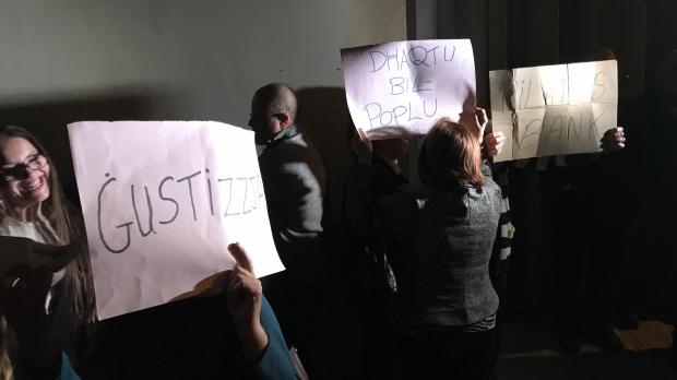 People have gathered outside Xarabank studios with makeshift placards against Dr Muscat