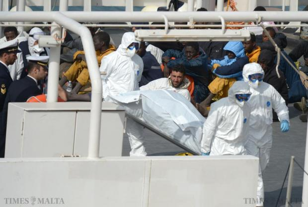 Rescued migrants watch as the bodies of 24 fellow migrants are offloaded by the Italian Coast Guard vessel Bruno Gregoretti at Boiler Wharf, Senglea in Malta on April 20. The 28 survivors continued on to Italy. Photo: Matthew Mirabelli