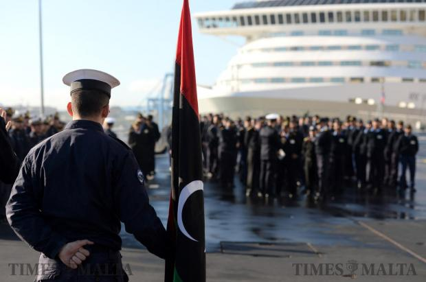 An Italian sailor holds the Libyan flag during a ceremony in which 89 members of the Libyan coast guard were presented with certificates. The ceremony took place on board the Italian training vessel San Giorgio in Valletta, Malta on February 8. Photo: Matthew Mirabelli