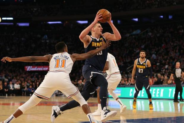 Denver Nuggets center Nikola Jokic (15) drives past New York Knicks point guard Frank Ntilikina (11) during the first quarter at Madison Square Garden. Mandatory Credit: Brad Penner-USA TODAY Sports