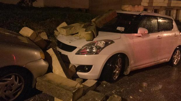Cars damaged by a falling wall in Baħar iċ-Ċagħaq.