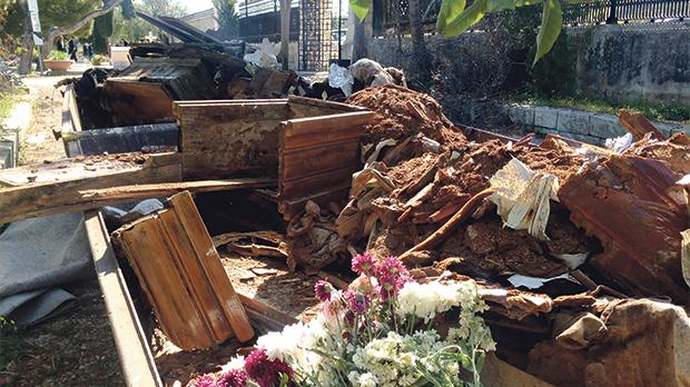 Skips overflowing with flowers, coffins and other materials.