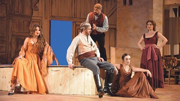 Oksana Volkova (Carmen) far left, Gabriele Ribis (El Dancaire) seated, Eduardo Santamaria Alvarez (El Remendado) standing, Lara Rotili (Mercedes) seated, Madina Karbeli (Frasquita) far right – a quintet of bandits in Carmen's Act II.