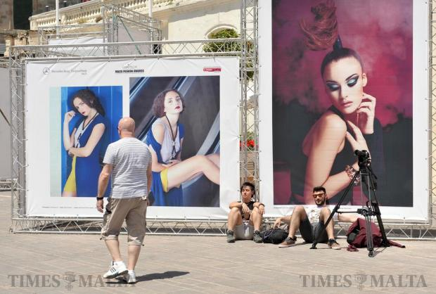 A model looks down onto a couple who are taking a rest on 'her' billboard which forms part of the Malta Fashion Week in St George's Square in Valletta on May 18. Photo: Chris Sant Fournier