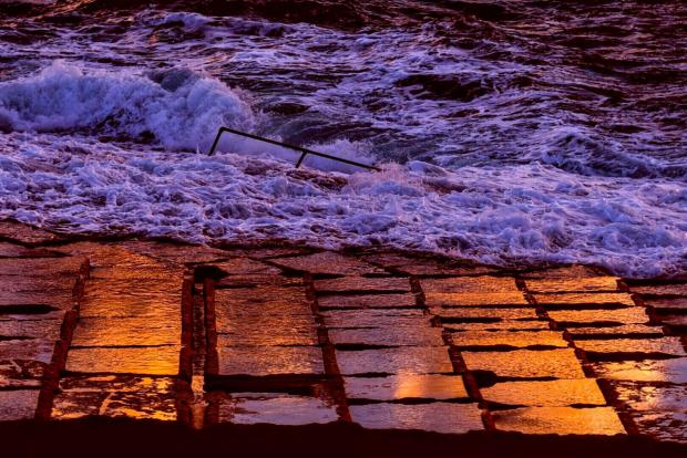 The rising sun gave a certain touch to the saltpans in Baħar iċ-Ċagħaq as the angry waves battered the coast on October 26. photo: Jonathan Borg