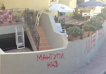 Red graffiti sprayed on the front garden of Buġibba properties.