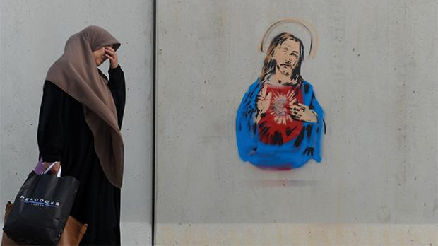 A Muslim woman walks by a street stencil portraying Jesus Christ at the Valletta bus terminus. Photo: Steve Zammit Lupi
