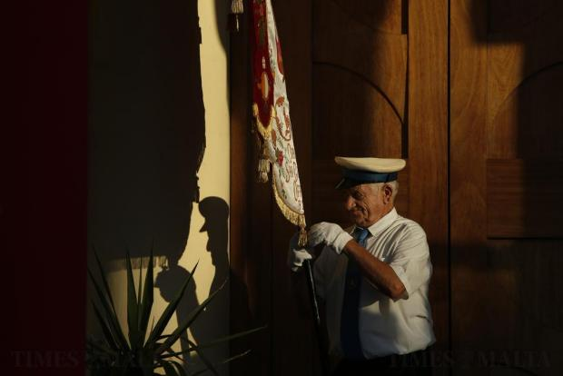 A bandsman prepares a banner before a procession during the religious feast of St Julian, patron of the town of St Julian's on August 28. Photo: Darrin Zammit Lupi