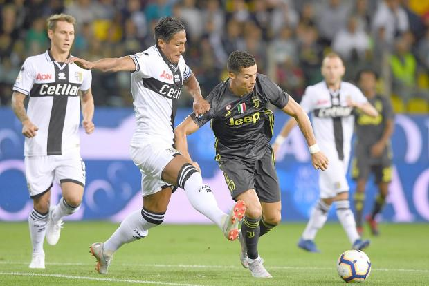Cristiano Ronaldo fends off the challenge of Bruno Alves, of Parma.