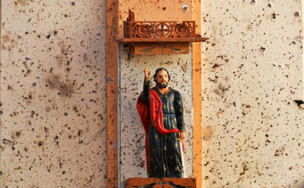 A statue of Jesus is surrounded by shrapnel from one of the explosions. Photo: AFP