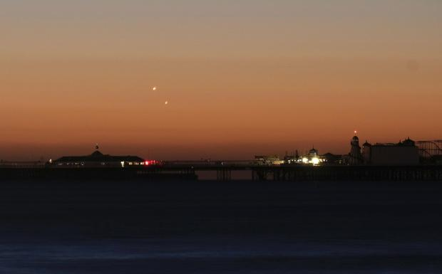 Handout photo of Venus (left) and Jupiter in the skies over Brighton Pier during a planetary conjunction.