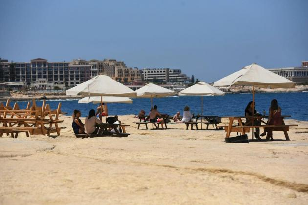 Why are tables and chairs appearing on Sliema's rocky beach?