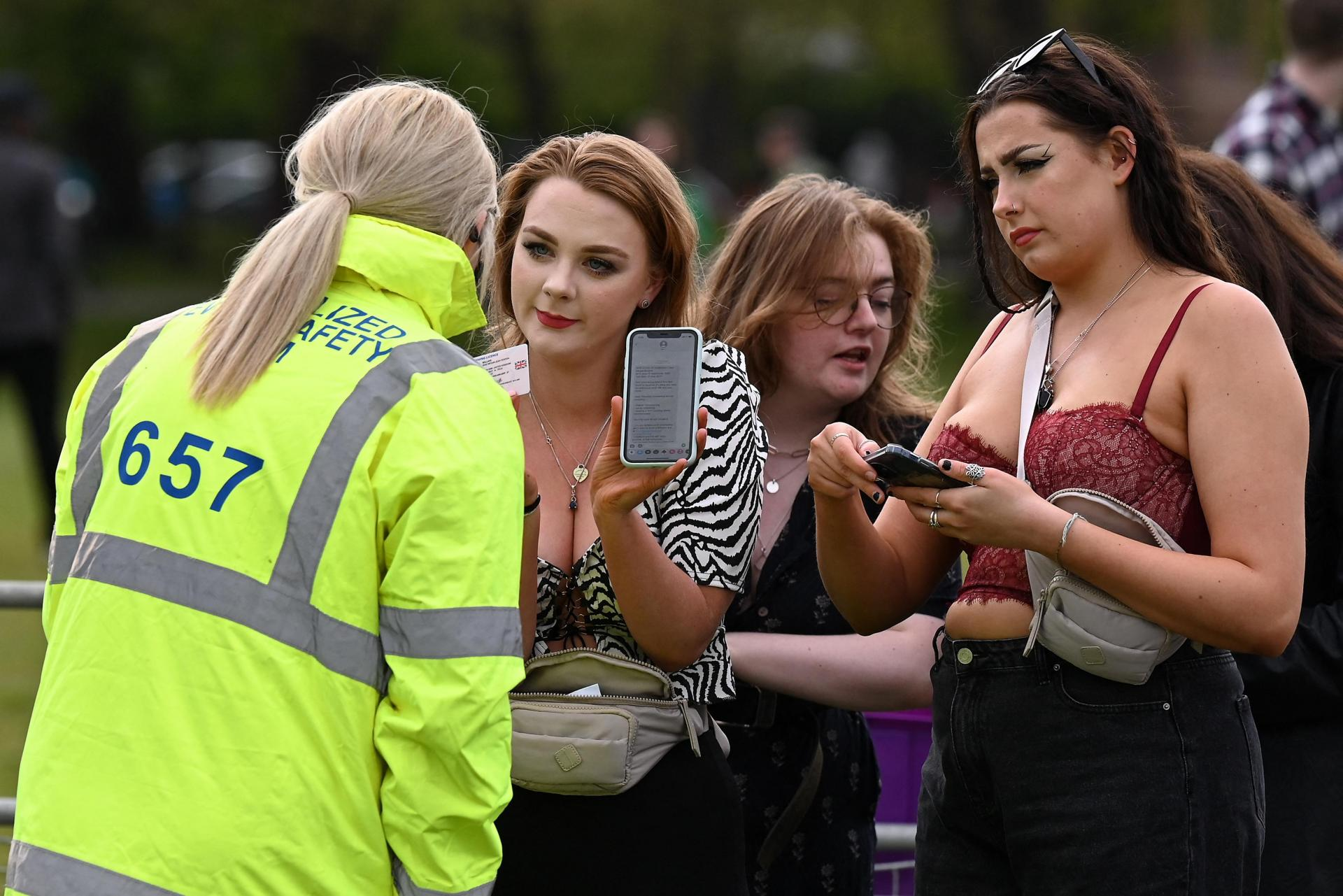 Concert-goers presenting a negative COVID-19 result on their mobile phone as well as their driving licence as they arrive at the concert venue.