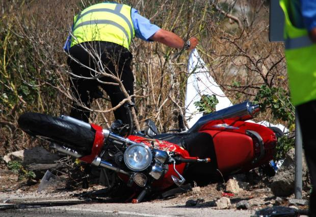 A traffic policeman lifts up the sheet covering the body of a motorcyclist following a fatal accident in Mgarr on June 28. Photo: Mark Zammit Cordina