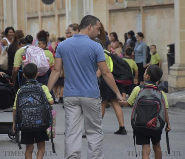 A man walks with his two children on the first day of school in Mosta on September 26. Photo: Mark Zammit Cordina