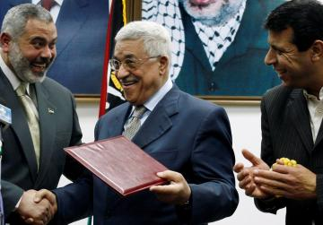 Palestinian President Mahmoud Abbas (C) gives the letter of appointment to Prime Minister Ismail Haniyeh (L) as then senior Fatah leader Mohammed Dahlan watches in Gaza February 15, 2007. Photo: Reuters/Suhaib Salem