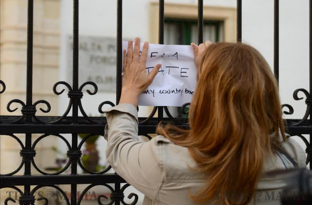 A lady places a placard outside the Police HQ during a protest organised by the Civil Society Network on November 5 in Floriana. The protestors called for the resignation of the Police Commissioner and the Attorney General. Photo: Matthew Mirabelli