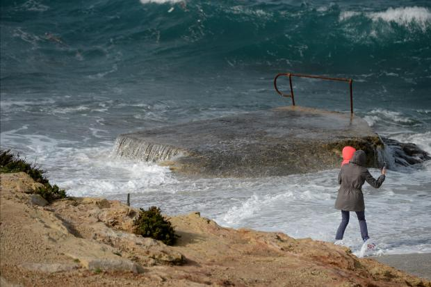 A wave catches a lady by surprise whilst taking a photo with her daughter in Bugibba on January 4. Photo: Matthew Mirabelli