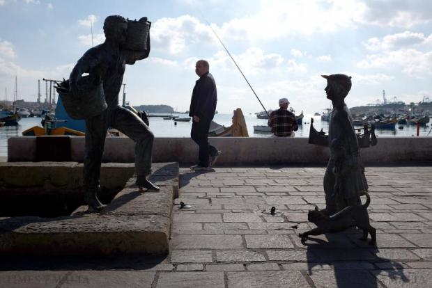 A man fishes behind a waterside sculpture in Marsaxlokk on December 19. Photo: Matthew Mirabelli