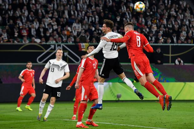 Germany's Leon Goretzka and Serbia's Milan Pavkov battle it out for the ball.
