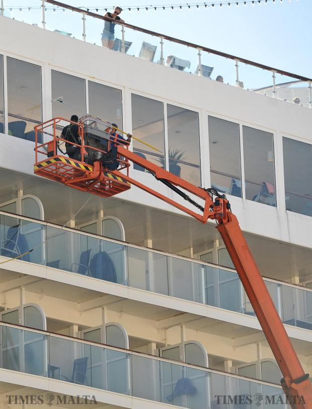 Cleaners wash the sides of a cruise liner in Grand Harbour on October 15. Photo: Chris Sant Fournier