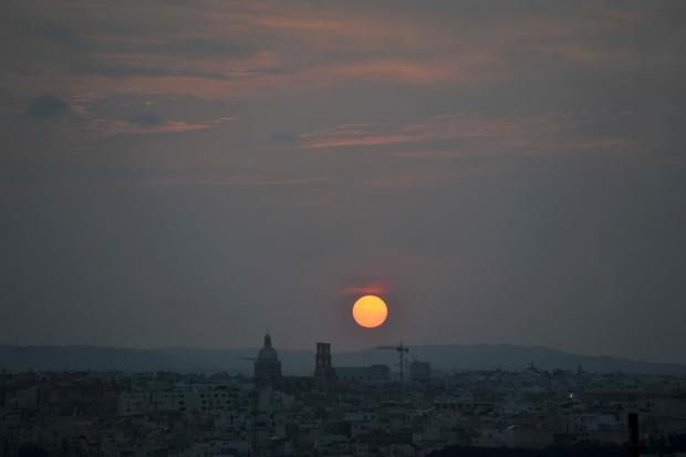 The sun sets behind the church of St Cajetan in Hamrun on August 26. Photo: Chris Sant Fournier