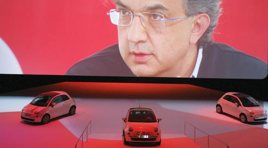 "Fiat Group Chief Executive Officer Sergio Marchionne appears on a video during a press conference to present the new Fiat 500 car in Turin. Fiat yesterday announced board approval for a ""demerger"" to hive off its non-car activities, a key step towards bos"