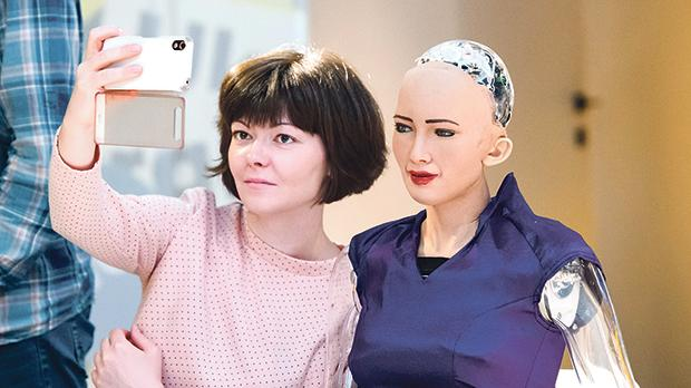 A woman takes a selfie with the social humanoid robot Sophia. Photo: paparazzza/shutterstock.com