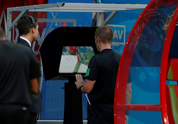 Referee Mark Geiger reviews an offside decision on VAR in World Cup match South Korea vs Germany.