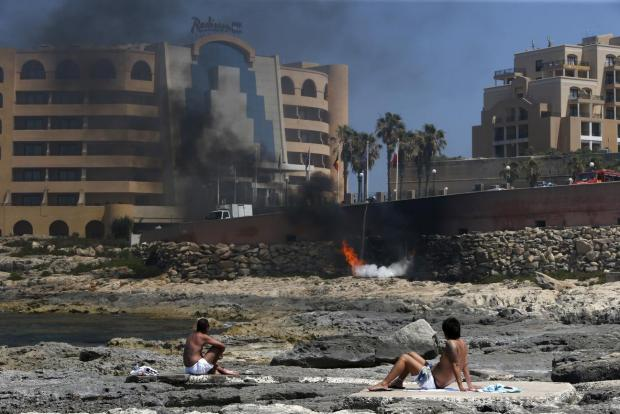 Sunbathing tourists watch firefighters tackle a blaze which broke out in a semi-basement store of the Radisson Blu hotel in St Julian's, on June 16. Photo: Darrin Zammit Lupi