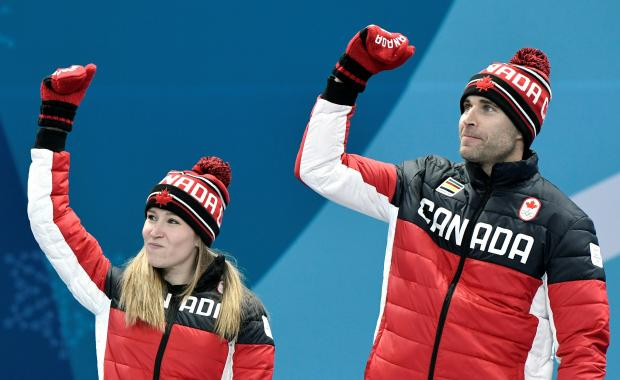 Gold medalists Kaitlyn Lawes and John Morris of Canada celebrate during the victory ceremony.