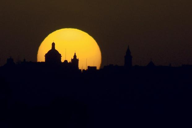 A detail of the Rabat-Mdina skyline, including one of the island's 300 churches, is silhouetted against the moon in the background, as if placing a halo on a sacred place. On March 5. Photo: Jonathan Borg