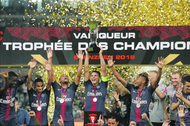 Paris St Germain players celebrate with the Super Cup trophy.