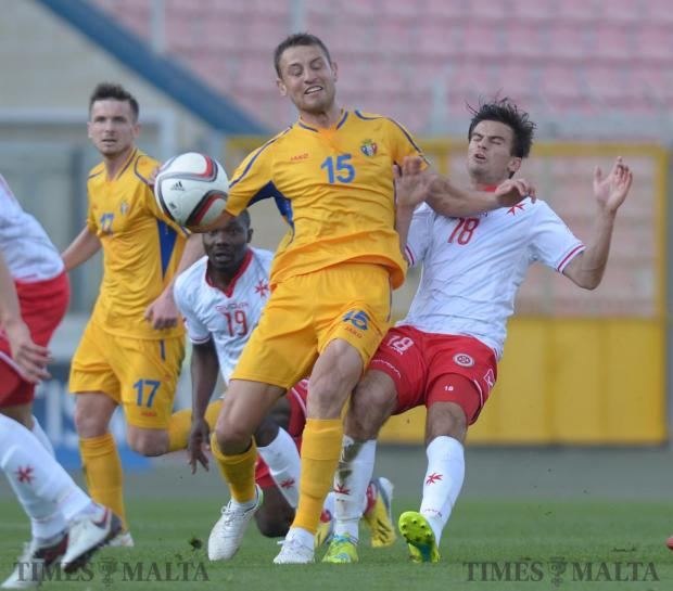 Moldova's Adrian Cascaval (left) blocks Malta's Bjorn Kristensen to the ball during an International friendly match at the National Stadium in Ta'Qali on March 24. Photo: Matthew Mirabelli