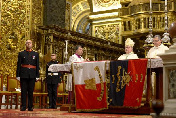 Apostolic Administrator Bishop Charles Scicluna delivers the final blessing during Mass at St John's Co-Cathedral, Valletta on January 16, marking the deposition of the army's old colours. The ceremony sees the AFM's blue standards, which are no longer in use, being presented to the Church to be placed alongside other old banners at the co-cathedral. Photo: Matthew Mirabelli
